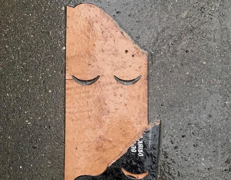Getränketragepappe auf nassem Asphalt, die an ein Gesicht erinnert.