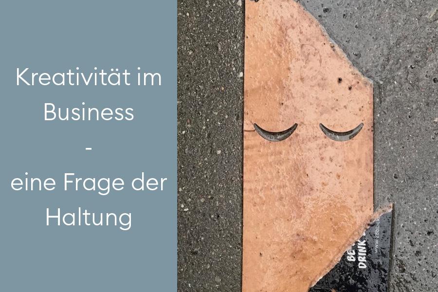 Kreativität im Business - eine Frage der Haltung - Bierpappe auf verregneter Strasse erinnert an ein Gesicht
